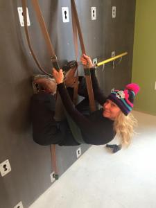 Serena Soffer hangs from the Kur yoga wall.  Kur is the only area studio with a yoga wall.