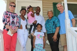 Maureen Mulligan, executive director of Coastal Habitat for Humanity with partner homeowner Dolan Williams and his three daughters, Hazel Samuels and David Butterfield, the organization's board president at the 17th home dedication ceremony Saturday of Father's Day weekend. Photo Mike Booth, Coaster.